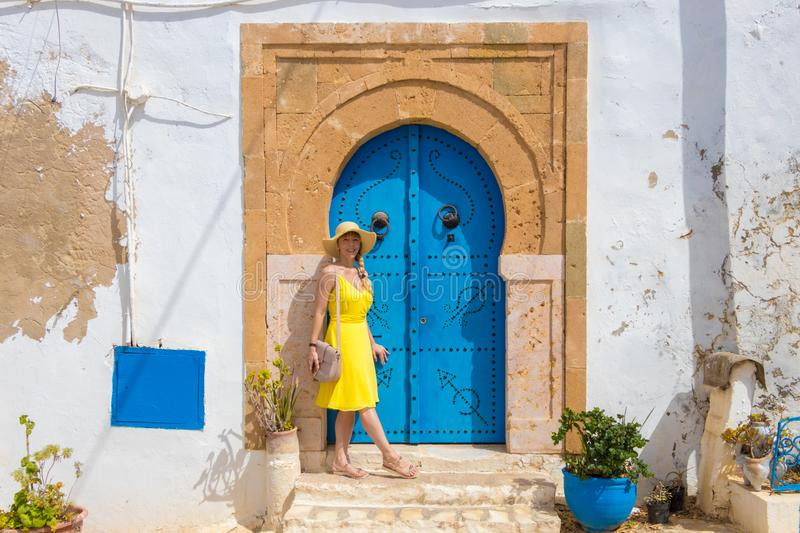 Young woman in yellow dress in front of the traditional door with pattern and tiles in Sidi Bou Said, Tunis, Tunisia.  royalty free stock photography