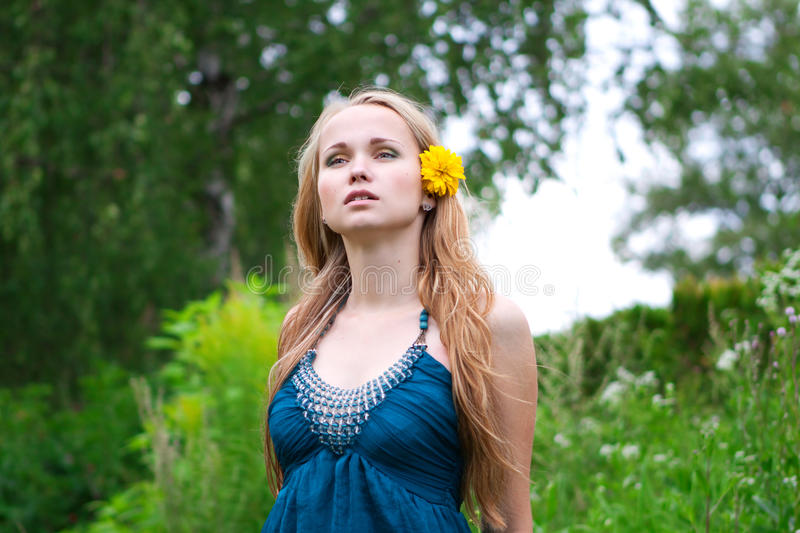 Young woman with a yellow flower in her hair stock photos