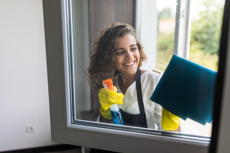 Young woman in yellow gloves cleaning window pane at home with rag and spray detergent. Cleaning concept royalty free stock photos