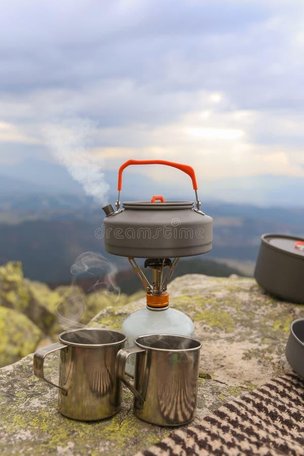 Hot camping teacup. Camping travel teapot and camping teacups in Carpathian mountains stock photos