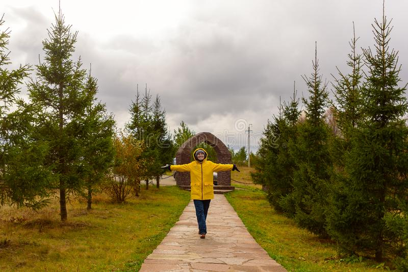 Young woman in a yellow raincoat walking along the path in the Park in cloudy weather with his hands in the rain rejoices, copy. Young woman in a yellow raincoat stock photos