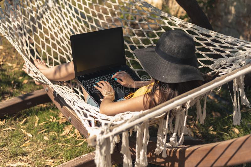 Young woman in yellow swimsuit and hat lying in hammock with laptop, work on vacation, freelance, remote work, online earnings stock images