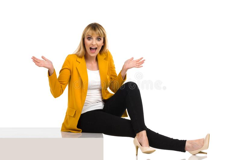 Surprised Woman Is Sitting On A Step, Gesturing And Shoutng. Young woman in yellow unbuttoned tail jacket, black jeans and high heels is sitting on a step stock photo