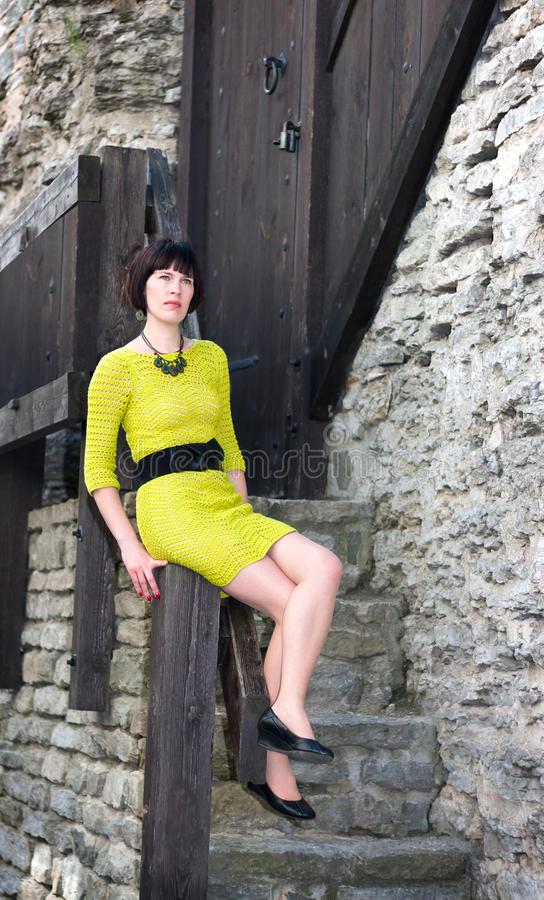 Young woman in yellowish dress sitting on a rail stock photo