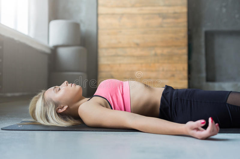 Young woman in yoga class, relax meditation corpse pose. Young slim blond woman in yoga class lay on floor. Girl do meditation corpse pose, savasana for stock images