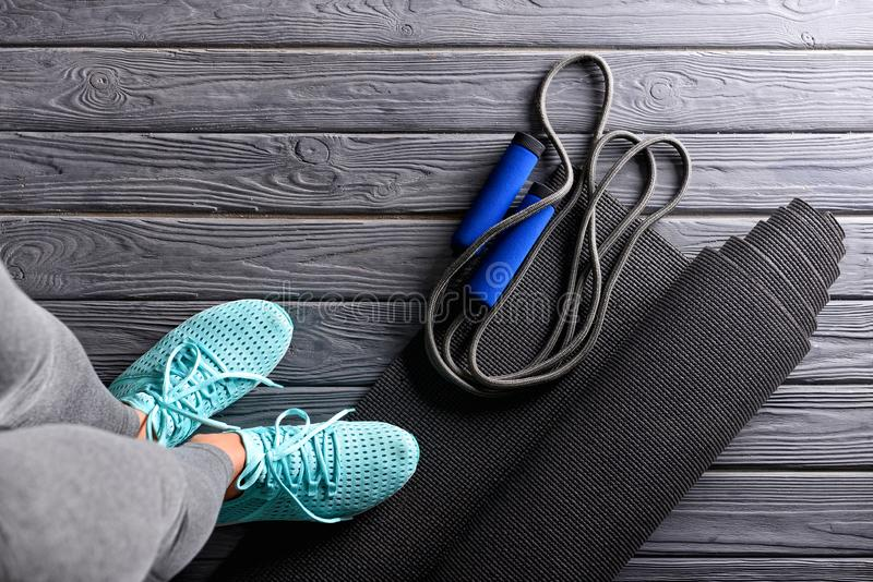 Young woman with yoga mat and skipping rope standing on wooden floor stock photography