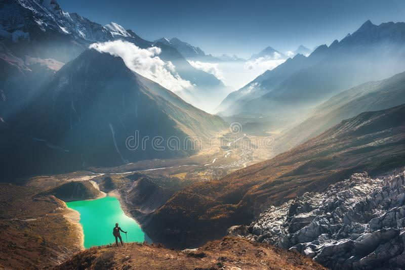 Young womanand beautiful mountain valley. Standing young woman on the mountain peak and looking on beautiful mountain valley with lake, river and hills at sunset stock image