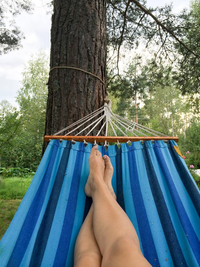 Young womanlaying in hammock. POV, naked legs stock image