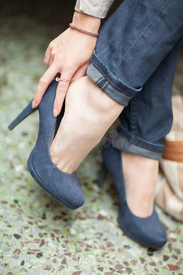 Young womans feet close up in a street cafe, urban mood. Blue jeans and high heels royalty free stock photos