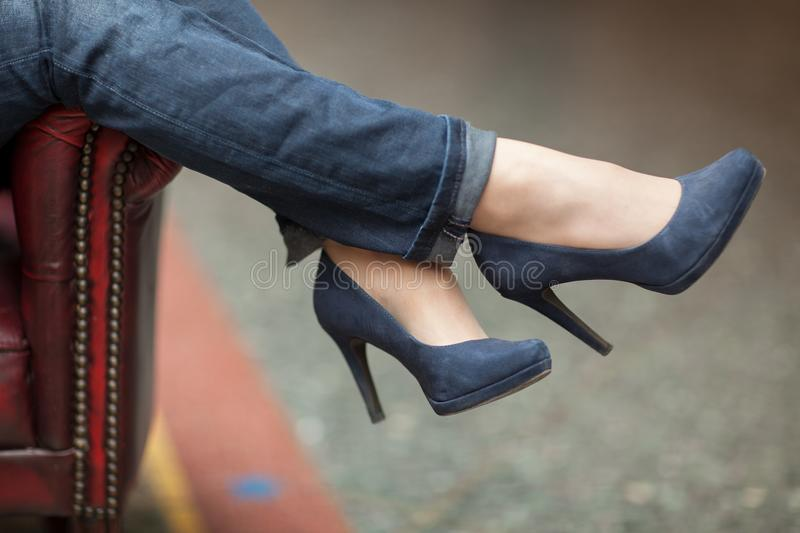 Young womans feet close up in a street cafe, urban mood. Blue jeans and high heels royalty free stock images