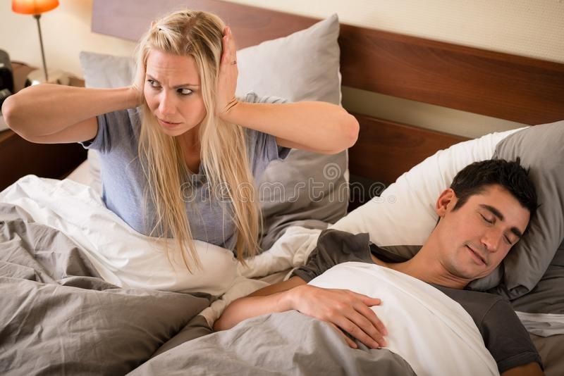 Woman annoyed by the snoring of her partner. Young women annoyed by the snoring of her partner sleeping in bed at night royalty free stock photos