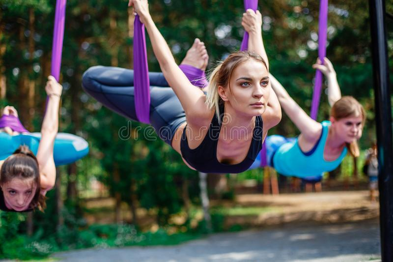 Young women, antigravity yoga exercises with a group of people outdoors. Aero fly fitness trainer. Young women, antigravity yoga exercises with a group of stock photo