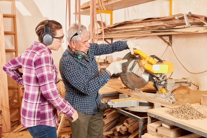 Apprentice and master at the chop saw. Young women as a carpenter. Apprentice and master work together on the chop saw stock photo