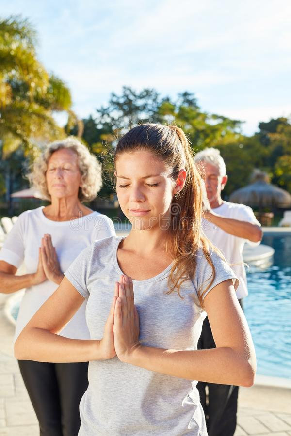 Young woman as a yoga teacher doing an exercise with seniors. Young women as a yoga teacher doing an exercise with seniors at the wellness pool royalty free stock photography