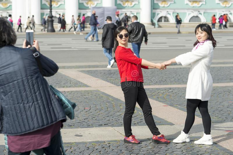 Young women of Asian appearance are photographed on Palace square against the background of the Hermitage in St. Petersburg, stock images