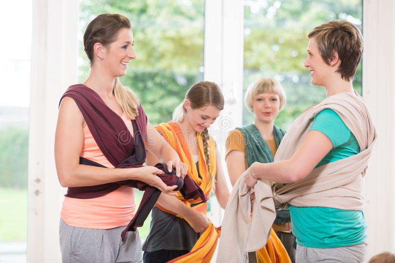 Young women learn how to use baby carriers for carrying children. Young women at baby course learn how to use baby carriers for carrying children stock photography