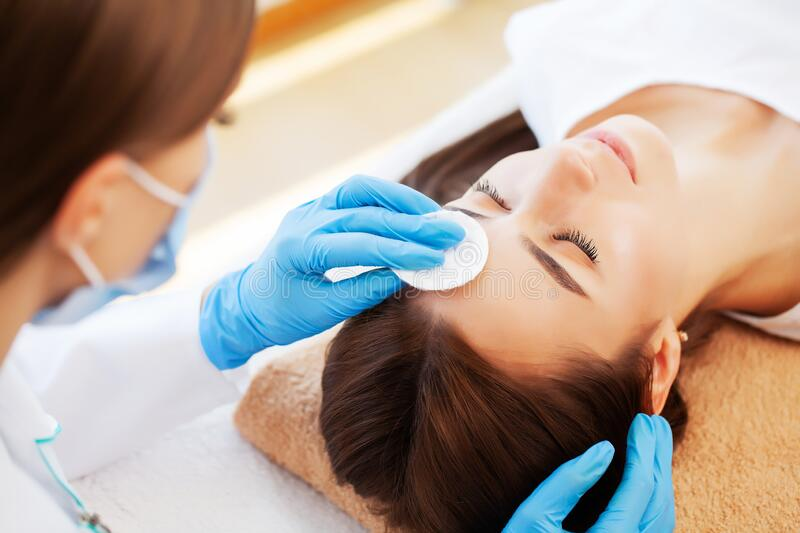 Young woman with beautiful face on facial massage in beauty studio royalty free stock photo
