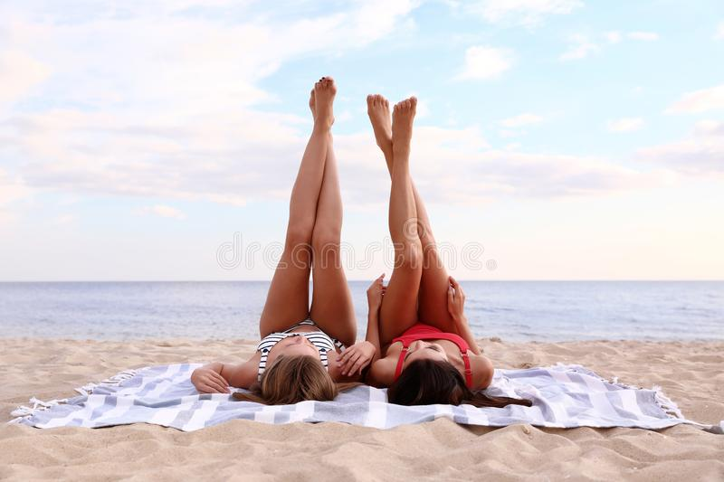 Young woman in bikini with girlfriend lying on mat. Lovely couple stock images