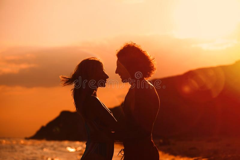 Young woman in bikini and her boyfriend on beach at sunset royalty free stock photography
