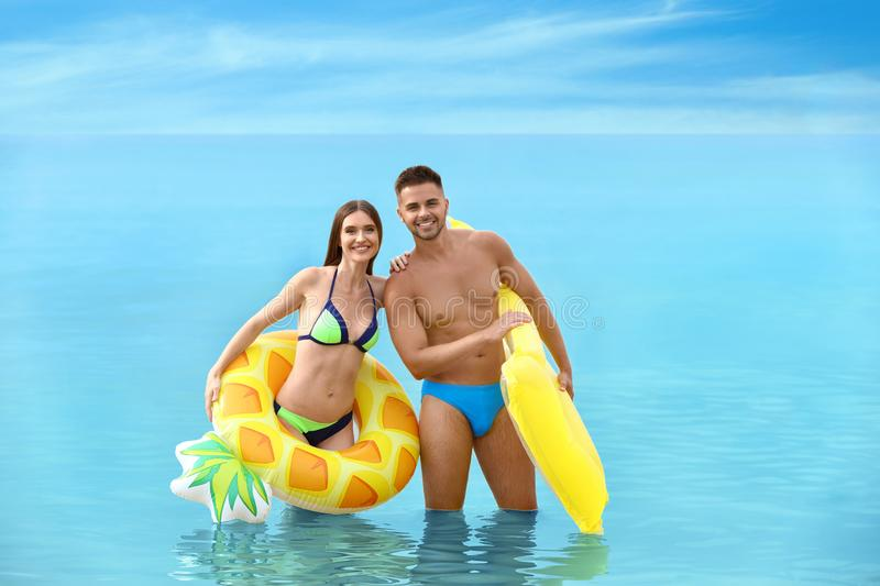 Young woman in bikini and her boyfriend with inflatable toys. Lovely couple stock photography