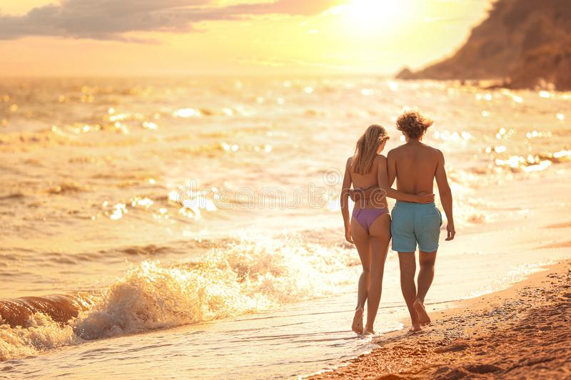 Young woman in bikini and her boyfriend walking on beach. Lovely couple stock image