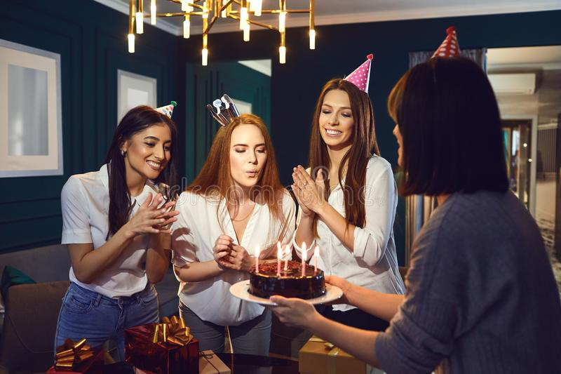 Woman with friends celebrating birthday. Young women blowing candles on cake while having birthday party gathering at home stock image
