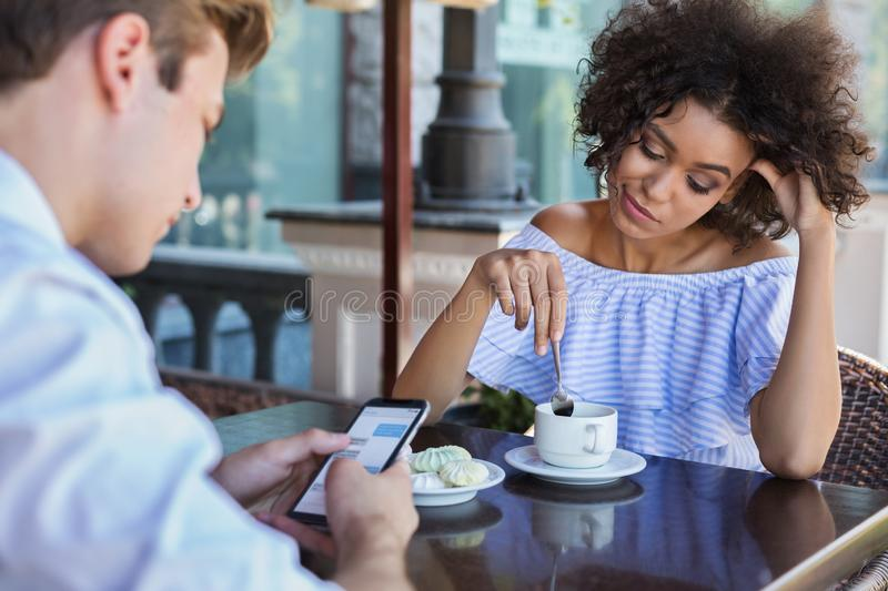 Young woman bored while her boyfriend using mobile phone royalty free stock image