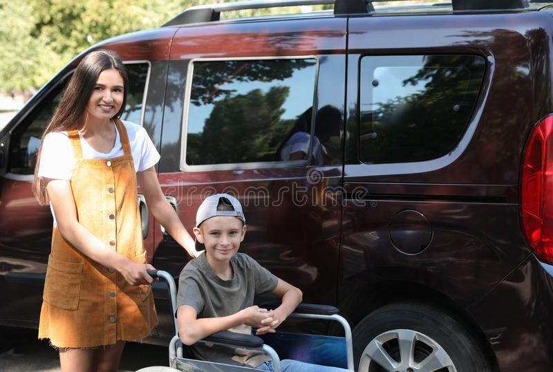 Young woman with boy in wheelchair near van royalty free stock images