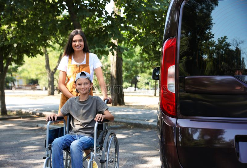 Young woman with boy in wheelchair near van royalty free stock photos