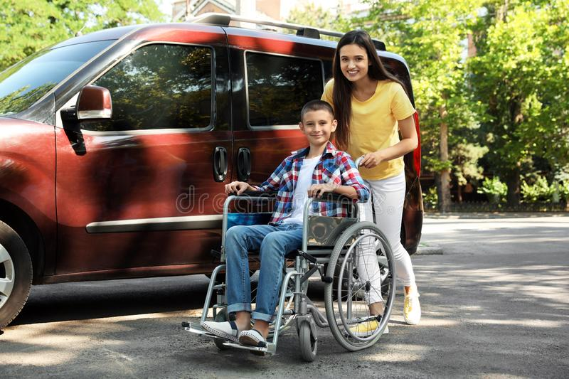 Young woman with boy in wheelchair near van stock photography