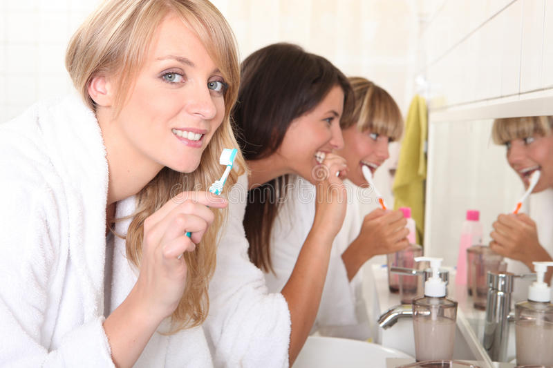 Young women brushing their teeth stock photos