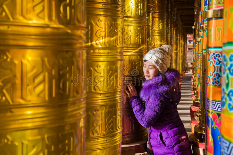 Young women and Buddhist Prayer Wheels royalty free stock image