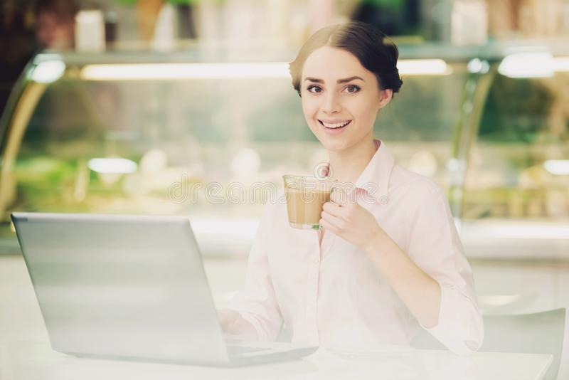 Young Women in Cafeteria with Coffe and Laptop. Young Attractive Smiling Brunette Woman Sitting at Table in Cafeteria with Coffe in Glass Cups and Laptop stock images