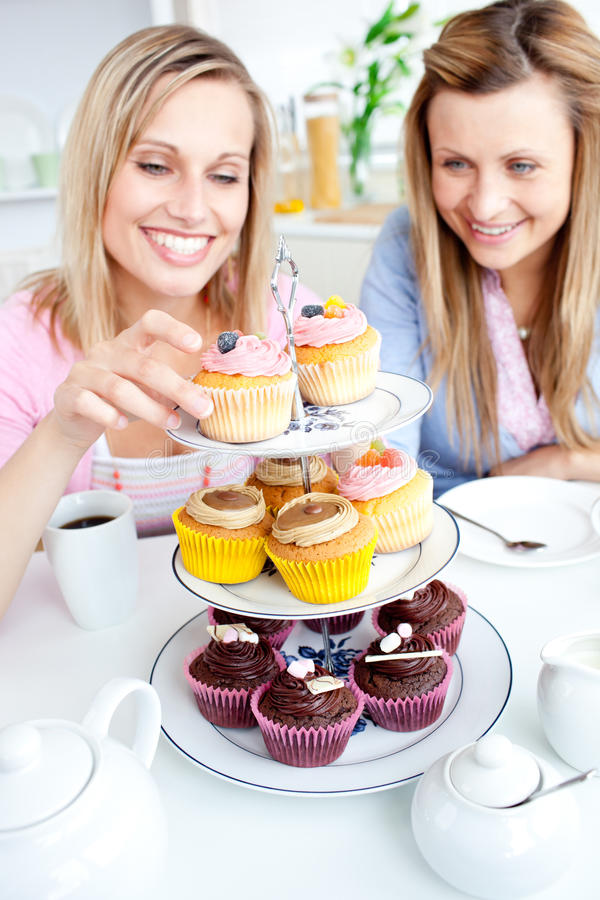 Young women choosing cupcakes royalty free stock photo