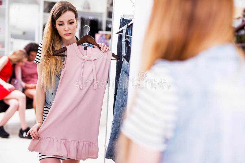 Young woman choosing new pink dress in a fashion boutique. Young women choosing new pink dress in a fashion boutique stock image