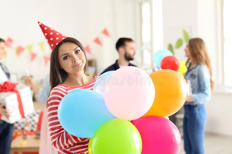 Young woman color air balloons at birthday party indoors. Young women color air balloons at birthday party indoors royalty free stock photography