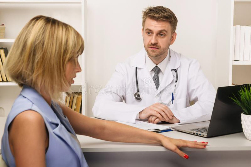 Young woman on a consultation with a male surgeon or therapist in his office royalty free stock image