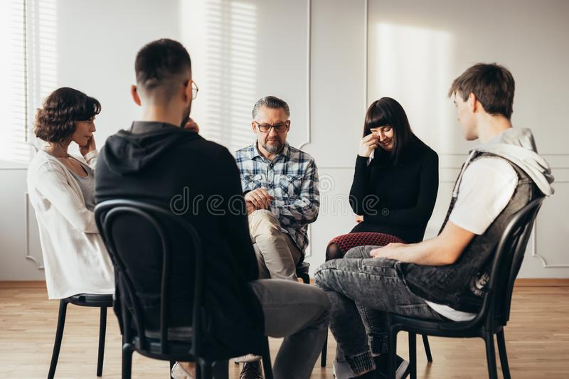 Young woman crying during widowers support group meeting stock photography