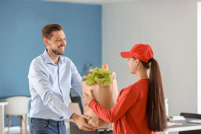 Young woman delivering food to customer indoors. Young women delivering food to customer indoors royalty free stock images
