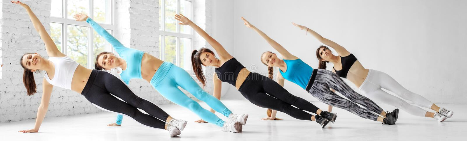 Young women do aerobics in the dance class. The concept of sports, a healthy lifestyle, fitness, stretching. Young women do aerobics in the dance class. Banner stock photography