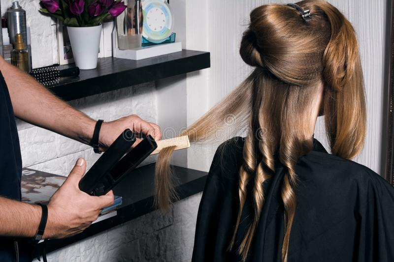The hairdresser does a hairstyle to a young woman. royalty free stock images