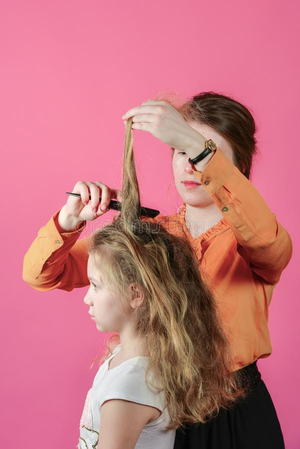 Young woman doing hairstyle girl, in the studio on a pink background stock photography