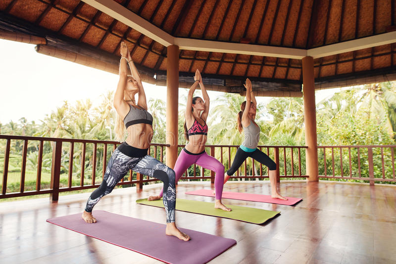 Young women doing the warrior pose in fitness class royalty free stock photos