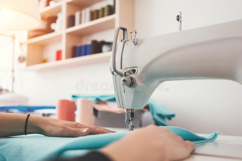 Young woman dressmaker sews clothes on a sewing machine in creative studio. Close-up photo of female hands and clo royalty free stock images