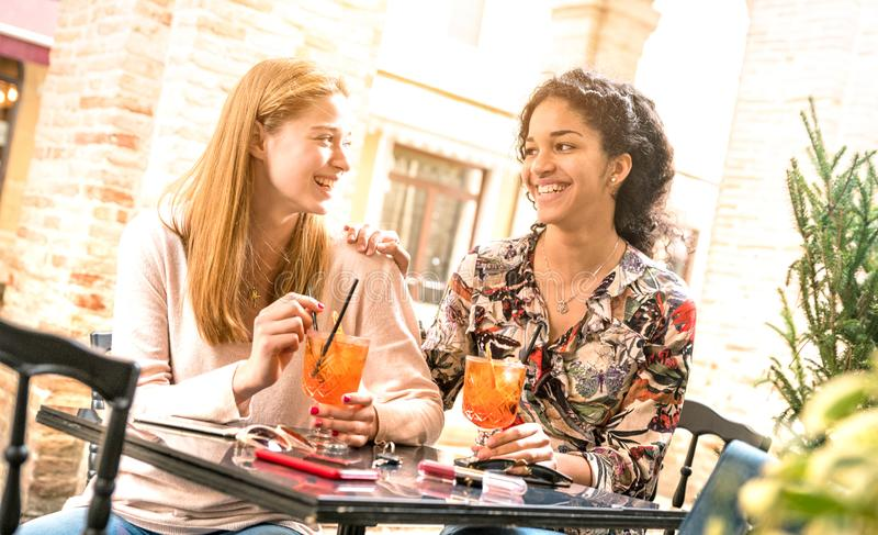 Young women drinking cocktails at bar restaurant outside on happy hour time - Friendship concept with millenial girlfriends royalty free stock images