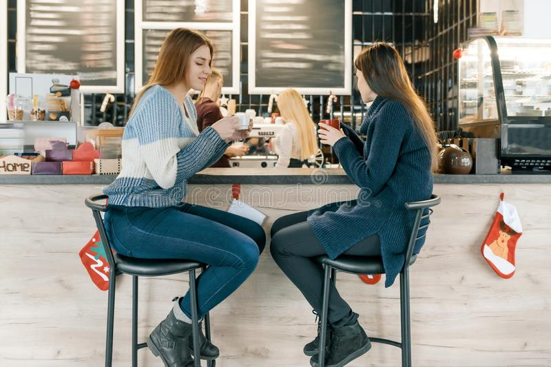 Young women drinking coffee in cafe, girls sitting near the bar counter stock photos