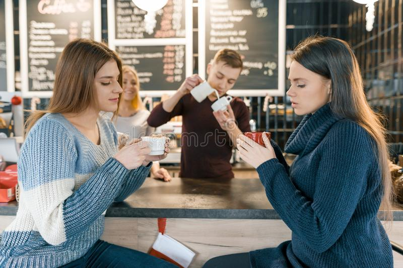 Young women drinking coffee in cafe, girls sitting near the bar counter royalty free stock photos