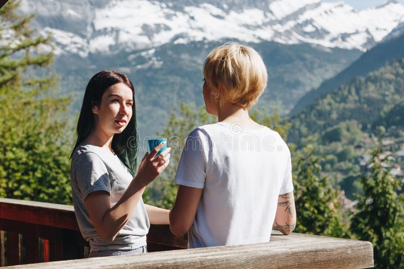young women drinking tea and looking at each other while standing on balcony in beautiful mountains mont royalty free stock photo