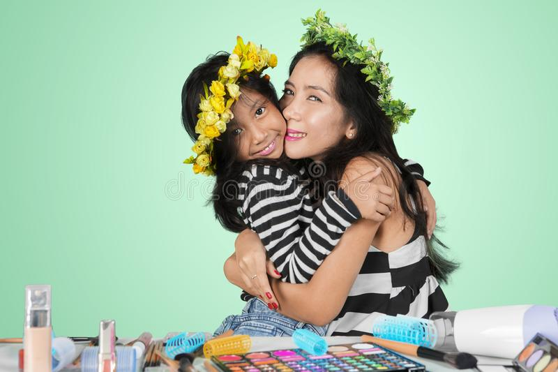 Woman embracing her child after makeup on studio stock photography