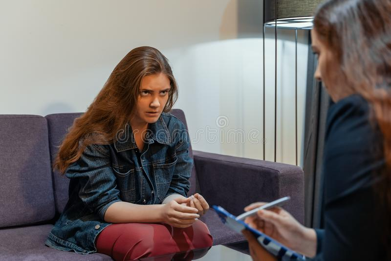 Young woman emotionally talks about her problems. Psychologist session, mental health and counseling. Psychological stock photo